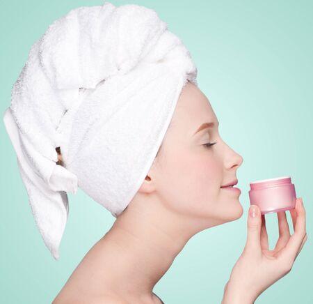 Beautiful woman tender jar of moisturizer cream. Close-up fresh young woman face photo