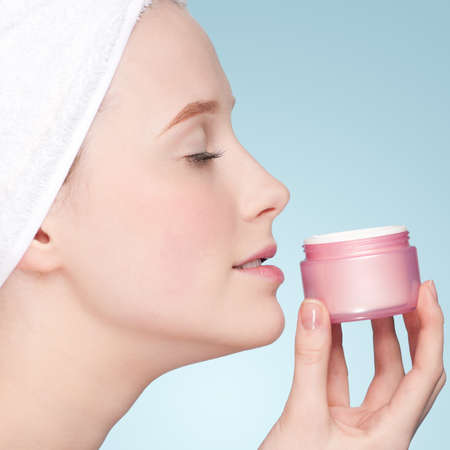 Beautiful woman smell jar of moisturizer cream. Close-up fresh young woman face photo