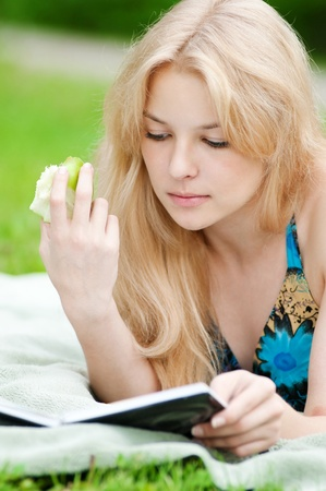 Beautiful young woman read book, at green summer park Stock Photo - 11468636