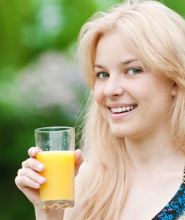 Young happy smiling woman drinking orange juice outdoor Stock Photo - 11468102