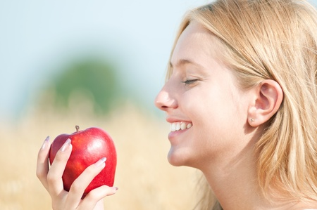 Young happy woman in wheat field with red apple. Summer picnic Stock Photo - 11469438