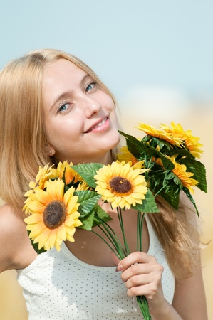 Young happy woman in wheat field with sunflower. Summer picnic photo