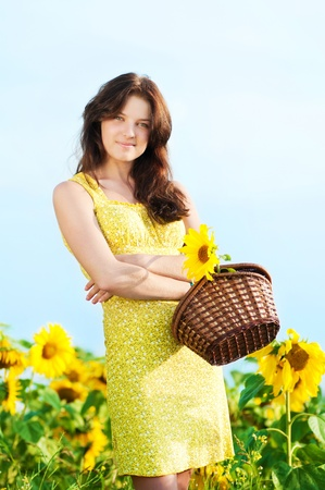 Young beautiful woman in a sunflower field. Summer picnic Stock Photo - 11468800