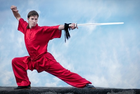 fu: Shaolin warriors wushoo man in red with sword practice martial art outdoor. Kung fu
