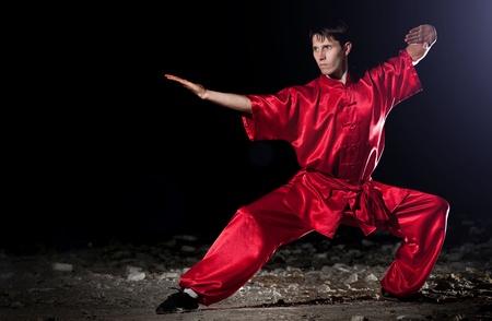 Shaolin warriors wushoo man in red practice martial art outdoor. Kung fu photo