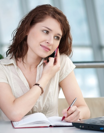 Smiling young business woman on phone taking notes in office photo