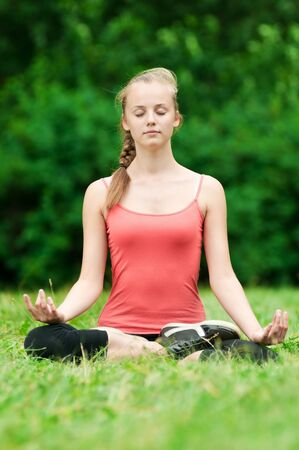 Beautiful young woman doing stretching exercise on green grass at park. Yoga Stock Photo - 11470456