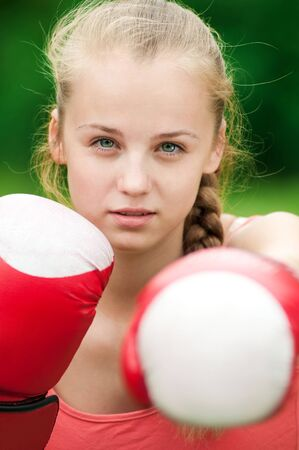 Beautiful young woman doing box exercise in red gloves at green park. Boxer photo