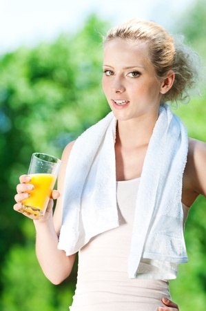Young woman drinking orange juice after fitness exercise Stock Photo - 11740336