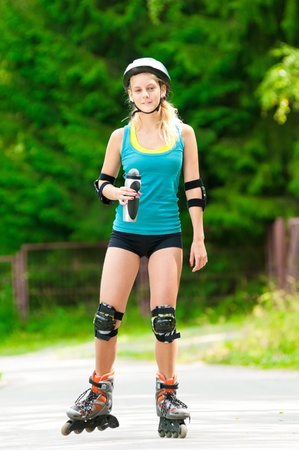 girl in sportswear: happy young woman on roller skates in the park Stock Photo