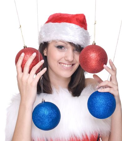 Close up portrait of brunette woman in santa claus dress, white fur playing with decoration balls photo