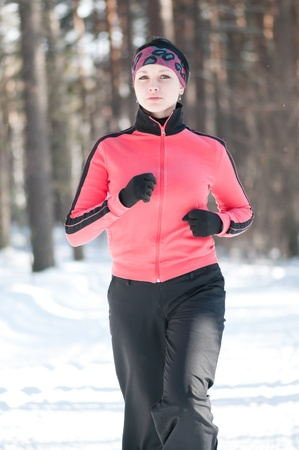 relaxion: Beautiful young woman running at winter forest