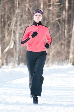 Beautiful young woman running at winter forest photo