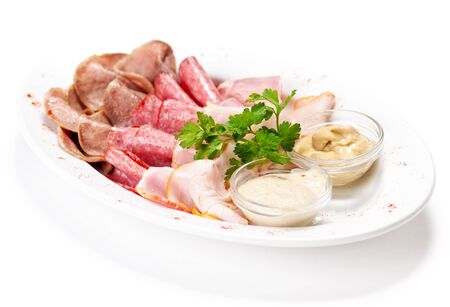 Meat delicatessen plate arranged with parsley and two sauce. Isolated on white photo