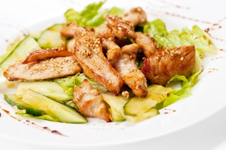 Grilled chicken salad with cucumber and lettuce. Isolated on white photo