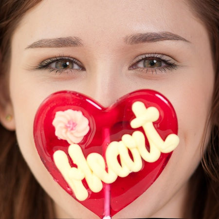 sugarplum: Portrait of pretty woman with candy heart. Love Stock Photo