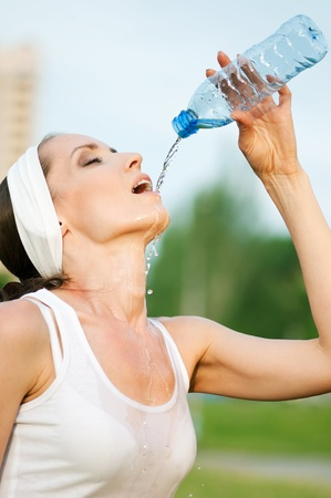 caucasian water drops: Young woman drinking water after fitness exercise