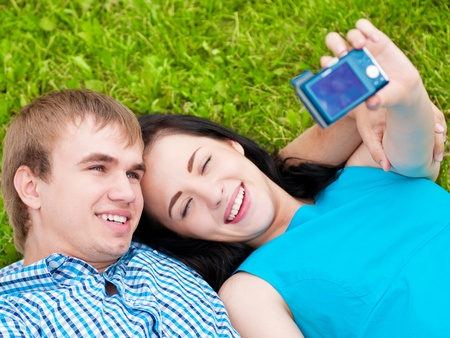 Young emotional happy teenage couple taking picture on grass in city park Stock Photo - 12126028
