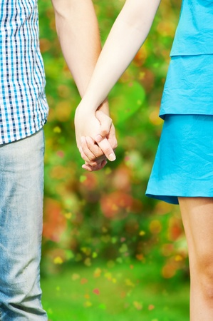 adult sisters: Concept shot of friendship and love of man and woman: two hands over green nature park