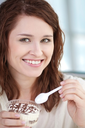 Young happy woman with cake at cafe photo