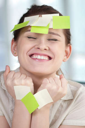 Portrait of emotional business woman with note papers photo