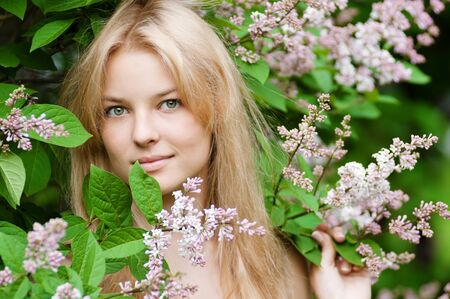 Beautiful young woman with a flower lilac over face