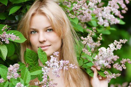 salud sexual: Joven y bella mujer con una flor de color lila sobre la cara