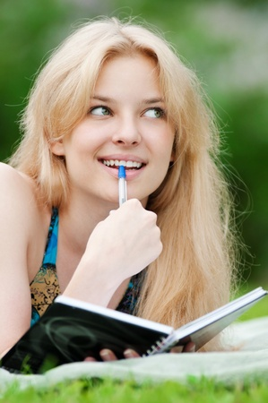 Beautiful young woman read book, at green summer park Stock Photo - 12129985