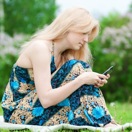 Young happy woman texting on mobile phone. SMS photo