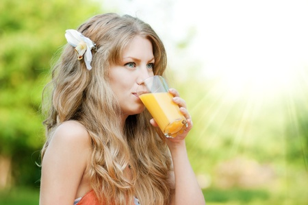 Young happy smiling woman drinking orange juice outdoor photo