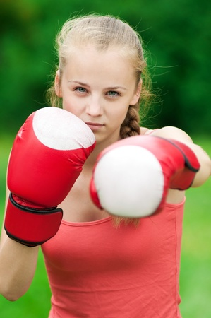 female boxer: Beautiful young woman doing box exercise in red gloves at green park. Boxer