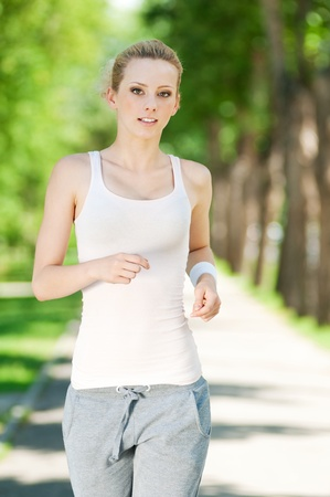 Beautiful young woman running in green park on sunny summer day Stock Photo - 12129997