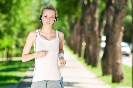 Beautiful young woman running in green park on sunny summer day Stock Photo - 12129991