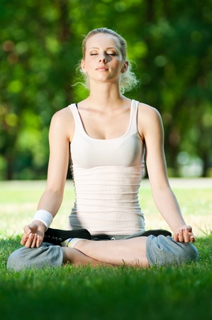 Beautiful young woman doing stretching exercise on green grass at park. Yoga Stock Photo - 12129932