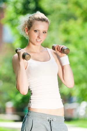 Beautiful young woman doing dumbbell exercise on green grass at park Stock Photo - 12129959