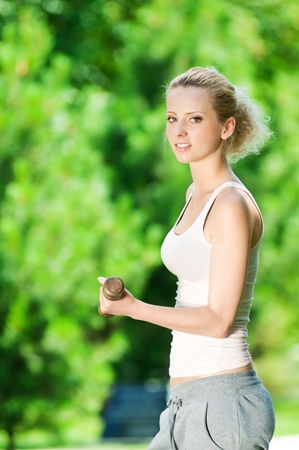 Beautiful young woman doing dumbbell exercise on green grass at park Stock Photo - 12129965