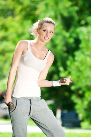 Beautiful young woman doing dumbbell exercise on green grass at park photo
