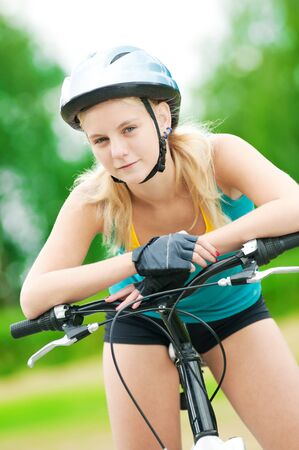 Portrait of pretty young woman with bicycle in a park - outdoor Stock Photo - 12129972