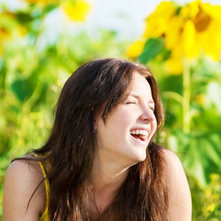 Young beautiful woman in a sunflower field. Summer picnic Stock Photo - 12129955