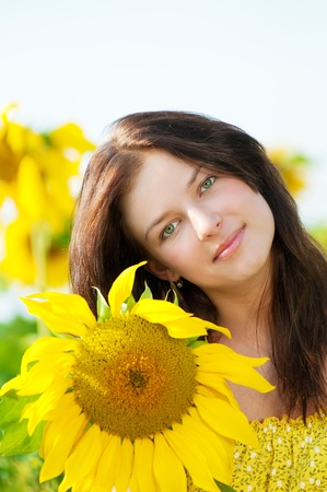 Young beautiful woman in a sunflower field. Summer picnic photo