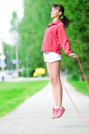 Summer vacation - teenage girl with skipping rope at park photo