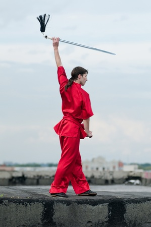 Shaolin warrs wushoo man in red with sword practice martial art outdoor. Kung fu Stock Photo - 12535263