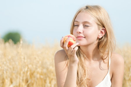Young happy woman in wheat field with peach. Summer picnic photo