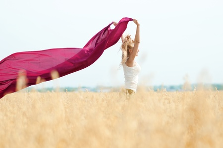 Young happy woman in wheat field with fabric. Summer picnic photo