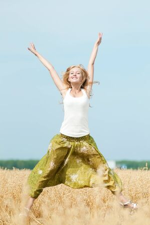 Young happy woman in wheat field. Summer picnic photo