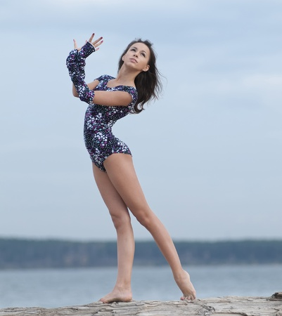 young professional gymnast woman dance - outdoor sand beach Stock Photo