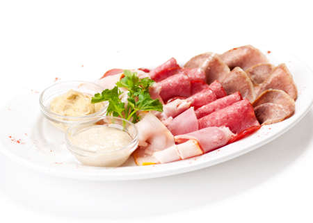 Meat delicatessen plate arranged with parsley and two sauce. Isolated on white Stock Photo - 12584699