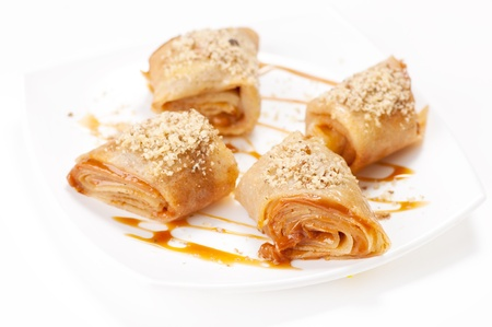 Rolled pancakes with caramel mousse and nuts. On white photo