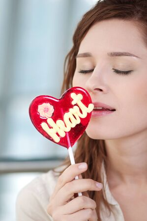 Portrait of pretty woman with candy heart. Love photo