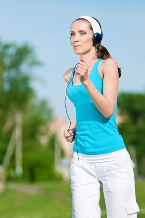Beautiful woman with headphones running in green park on sunny summer day Stock Photo - 12535391
